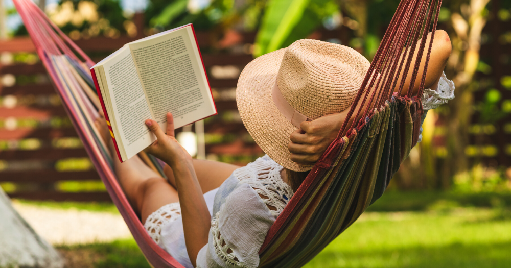 woman relaxing in her backyard hammock while reading a book in the sun