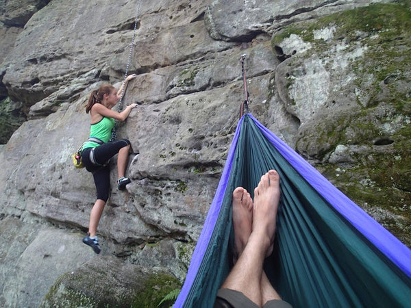 Woman climbing as man hangs in a hammock on the side of a cliff