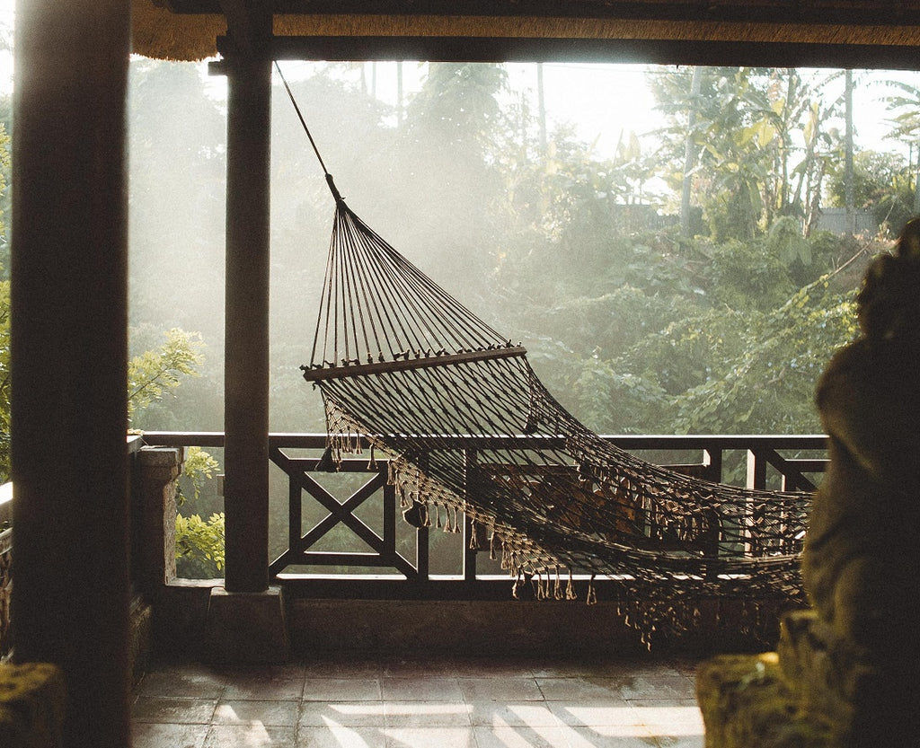 Rope hammock hangs on porch in natural light