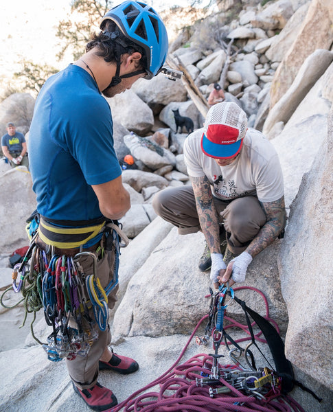 Rock climbers inspect their gear and make the necessary knots before their climb