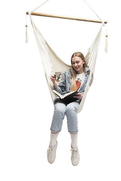 Girl reads a book and drinks coffee while sitting in a specialty Mayan hammock chair.