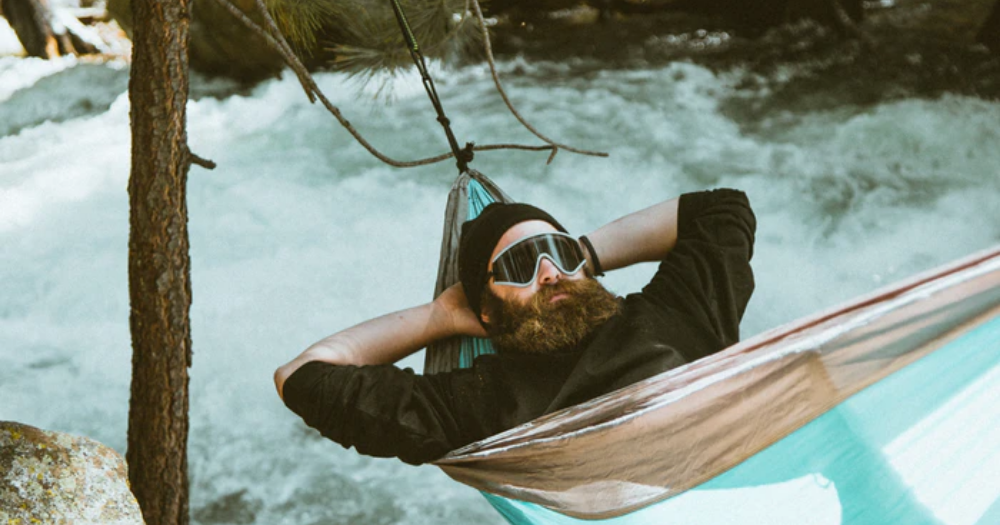 man hanging outside in this hammock in the winter near a river