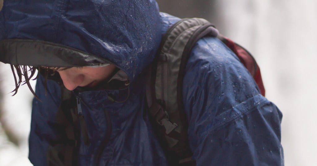 Person camping wearing a rain coat and backpack soaking wet form the rain