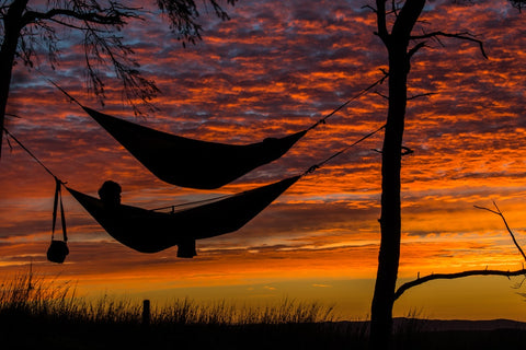 Two hammocks hang, one above the other, silhouetted against a beautiful orange sunset.