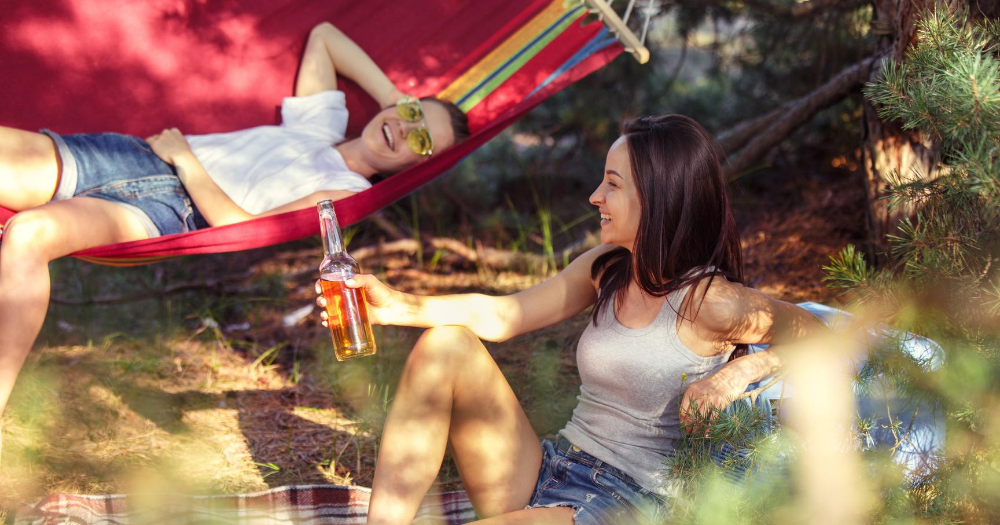 two women enjoy the outdoors while on their hammock