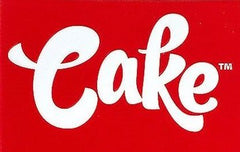 """""""Cake"""" is written in loopy, white text. The rectangular background is red."""