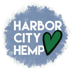 """A blotchy blue-grey circle has the white text """"Harbor City Hemp"""". A heart is drawn next to it, outlined in black and filled with green."""