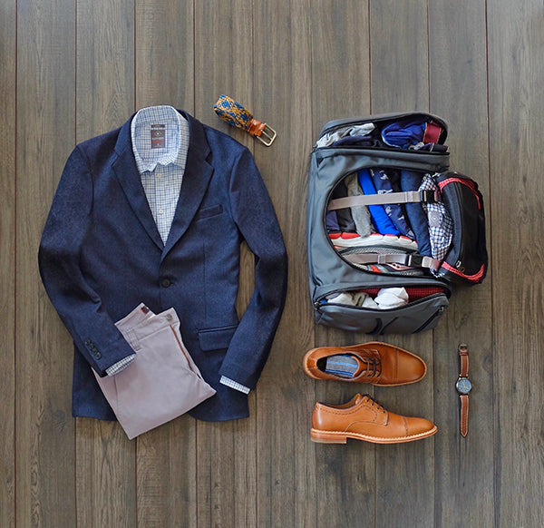Outfit for the plane next to backpack packed with our travel capsule wardrobe.