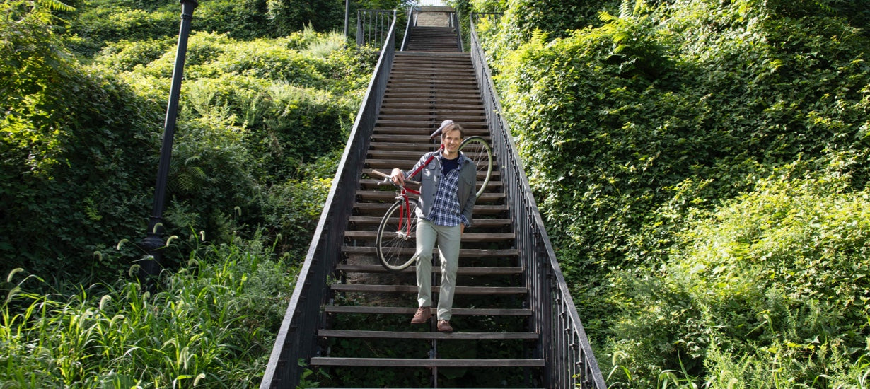 Stefan carries his bike down steps lined with greenery.