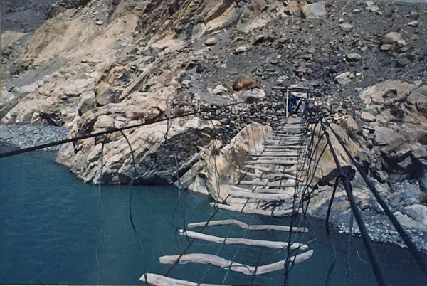 An eye-level view of a rickety bridge high up over a river in Northern Pakistan.