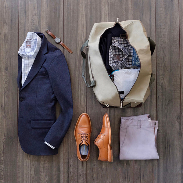 Outfit for the plane next to a duffel bag packed with our travel capsule wardrobe