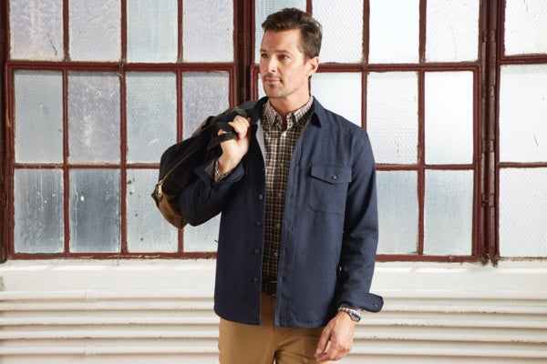 Our Gramercy Shirt Jacket in Blue Hour layered over a dress shirt, with a bag slung over the model's shoulder.