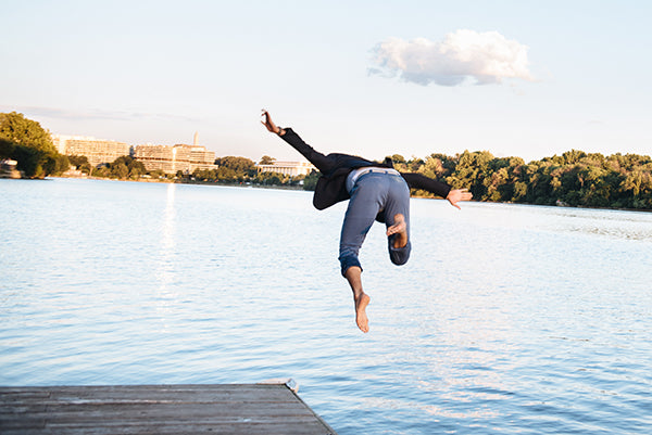 A man jumping into a lake while wearing rolled up blue chinos and a travel blazer.