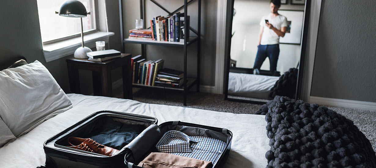 A man in his bedroom with a open suitcase on the bed, in the midst of packing.