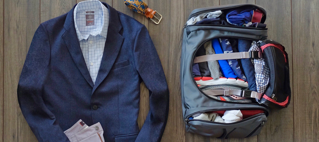 A duffle bag packed full with a suit laid out next to it.