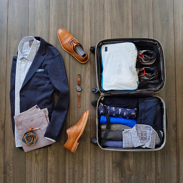 Outfit for the plane next to a rollerboard suitcase packed with our travel capsule wardrobe