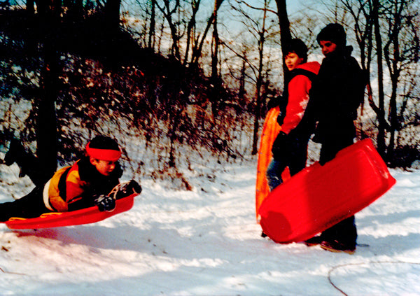 A vintage photo of three young boys wearing orange + black while sledding in the snow.
