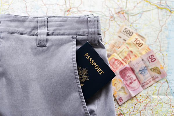 A pair of Bluffworks Chinos on a map of Mexico with foreign currency and a passport.