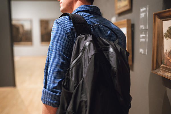 Tourist in museum wearing a backpack.