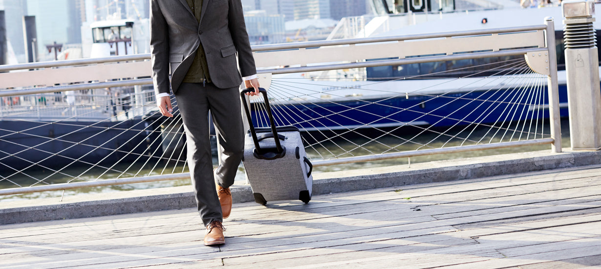 A business traveler with a roller board suitcase.