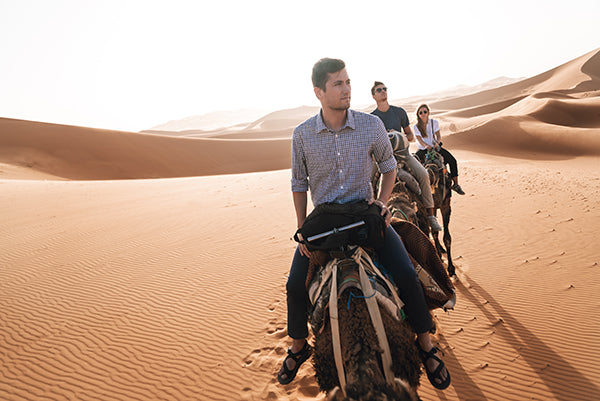 Riding camels in the desert while wearing Bluffworks.
