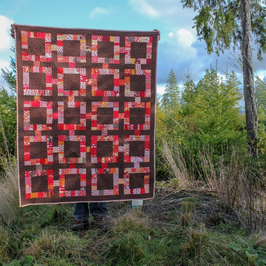 Quilt pattern in a mid-century modern theme in red and brown with blue sky behind