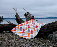 Load image into Gallery viewer, Modern quilt on beach in orange, red, green, gray and white from a pattern called geometric patchwork