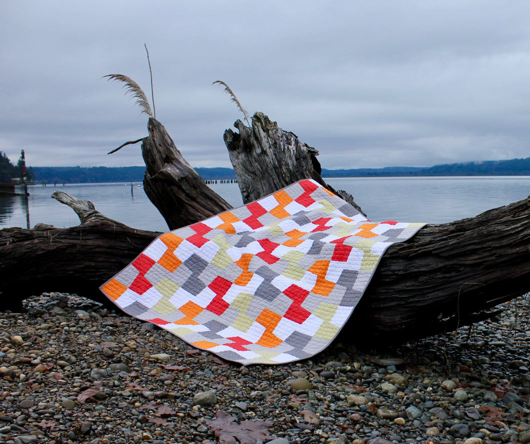 Modern quilt on beach in orange, red, green, gray and white from a pattern called geometric patchwork