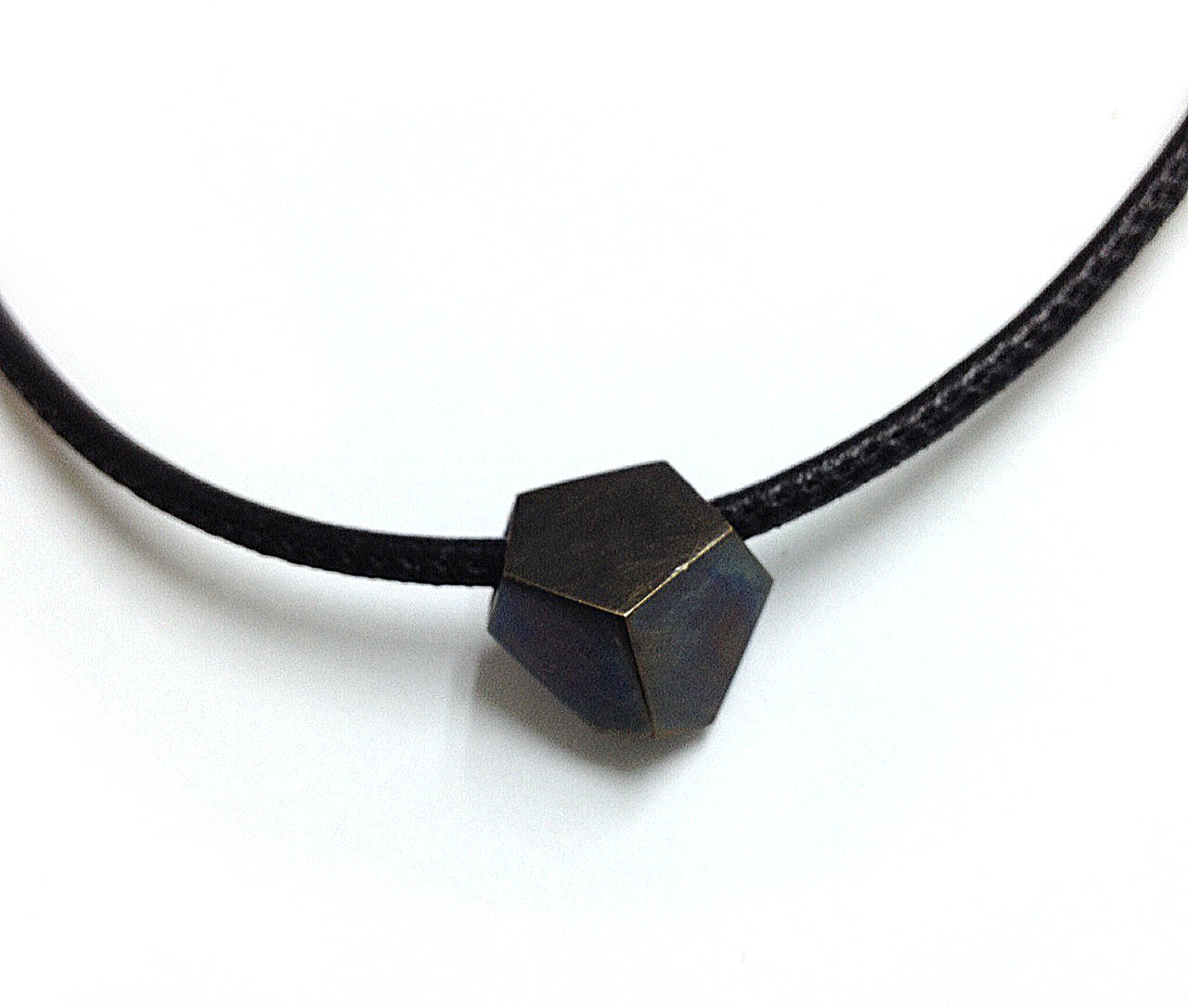 Geometric hexagon shaped oxidized bronze charm on stitched leather chord.  Choker necklace