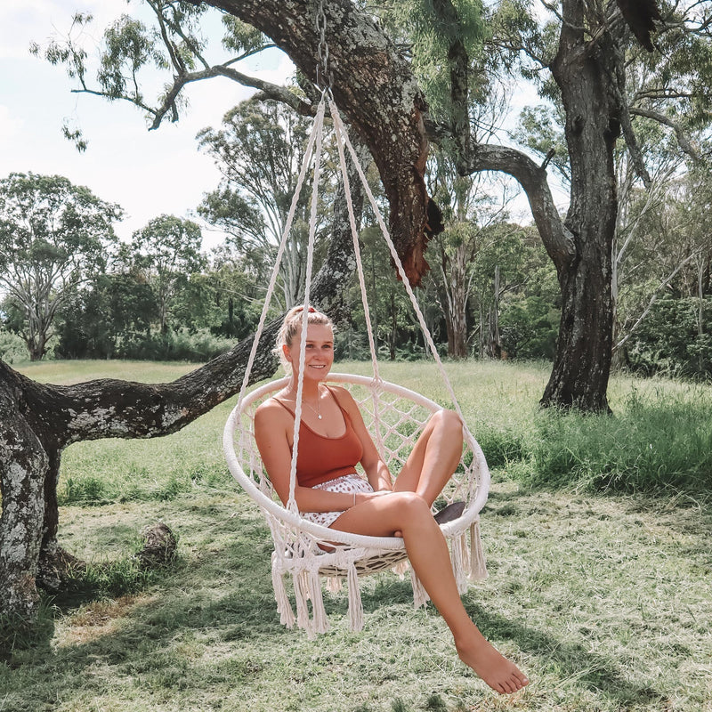 pretty girl relaxing outdoor on a hanging macrame hammock swing chair
