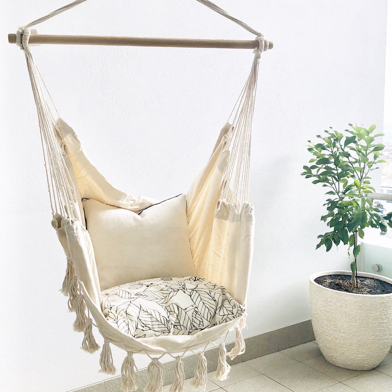 boho hanging hammock chair with cushions and tall green plant in a white pot