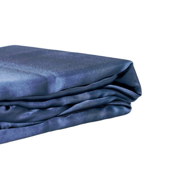 folded navy blue satin quilt cover set on a white background from Ivory & Deene