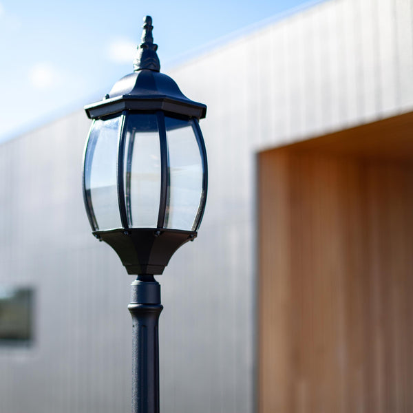 Black Victorian Garden Lamp Post next to a corrugated iron house with a timber front door