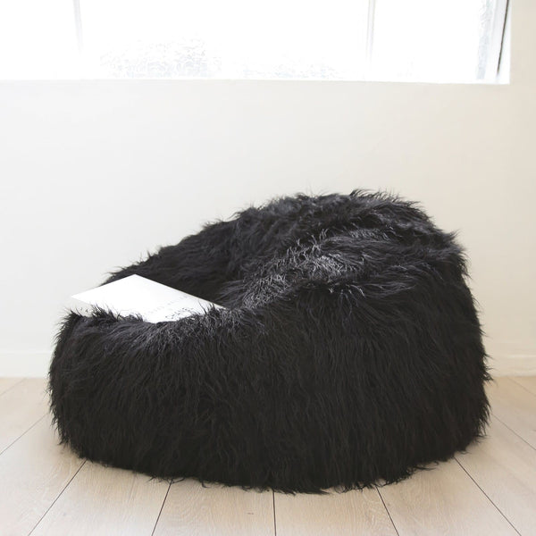 black shaggy fur beanbag on a wooden floor under a warehouse window