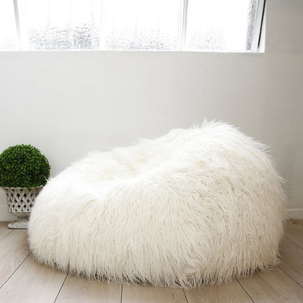 white shaggy fur bean bag on wooden floor with green plant next to it under a warehouse window