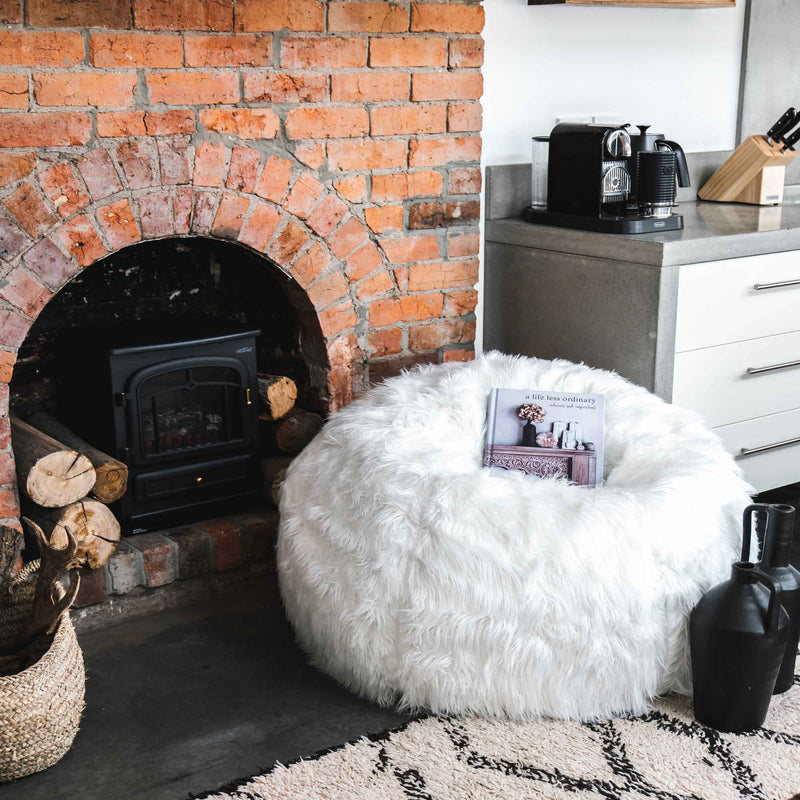 white lush fur bean bag next to a red brick fireplace