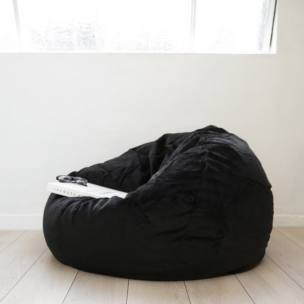 white coffee table book resting on a black fur bean bag on a white background
