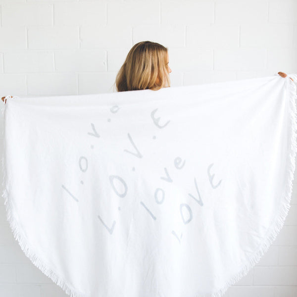 girl holding a round beach towel with love printed on it