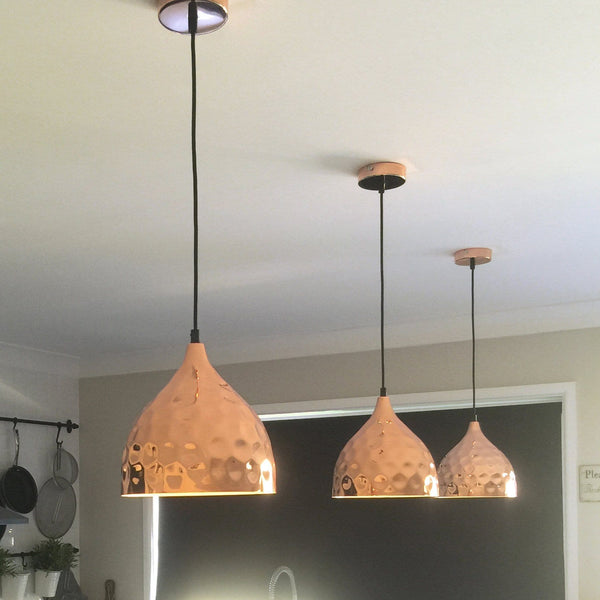 copper pendant lights hanging in a kitchen with a window in the background