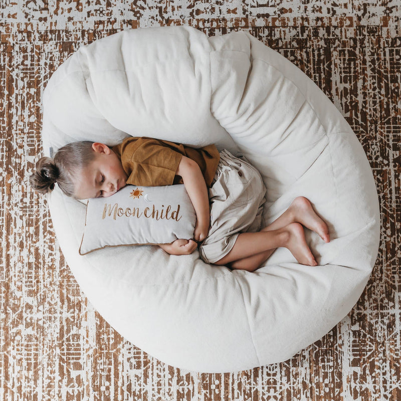 cream beanbag lounger chair with child relaxing with a cushion