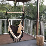 white hammock with black tassels hanging under a balcony in a lush garden next to a tree stump table