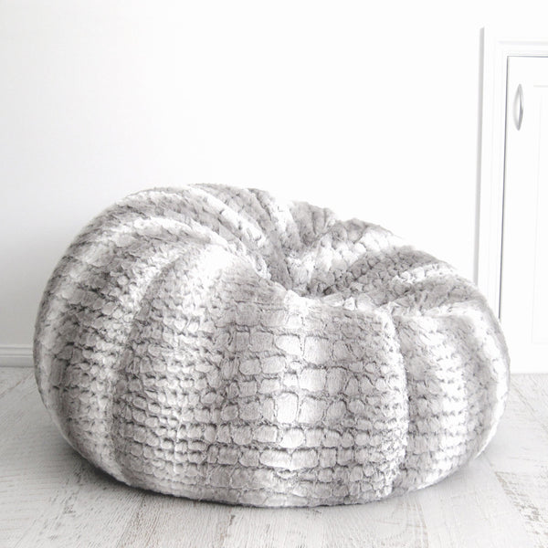 silver grey husky fur beanbag on a wooden floor with a white door behind