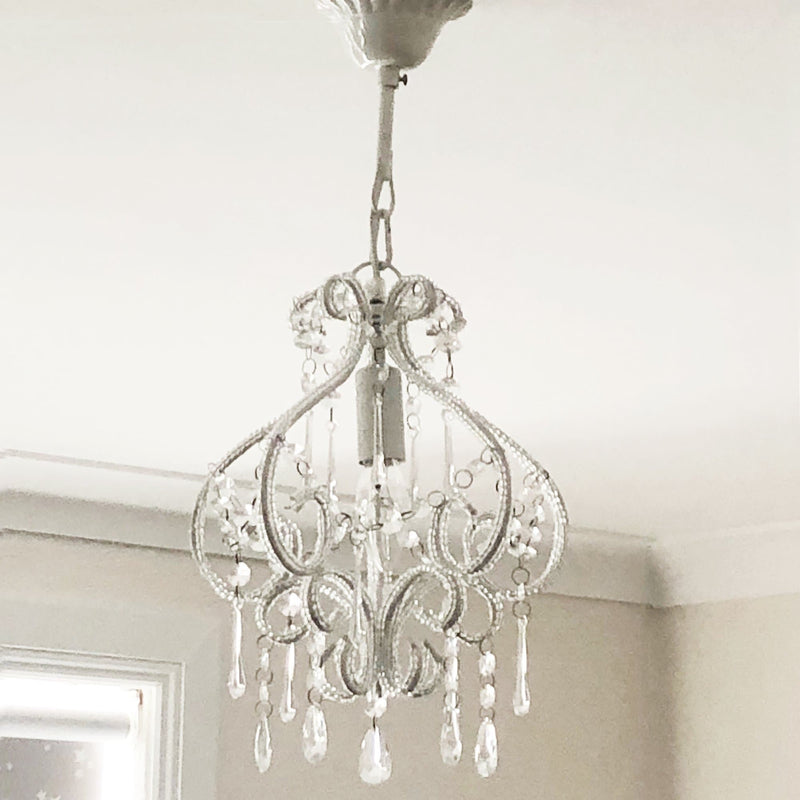 white darling chandelier hanging in a bedroom with a window in the background