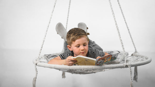 round nest swing hammock with child reading a book