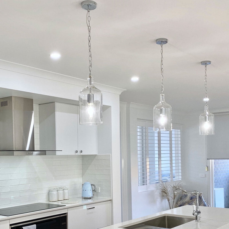 glass jug pendant light hanging in a white kitchen with smeg appliances and white window shutters
