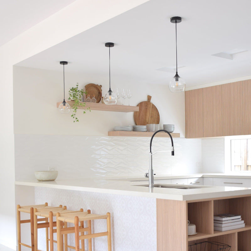 glass ball pendants lights hanging over a kitchen bench