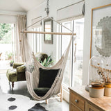 cream rope hammock chair with green velvet cushions over a cowhide rug in a boho setting