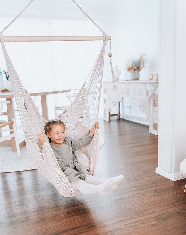cute girl swinging in a macrame hammock chair over a wooden floor