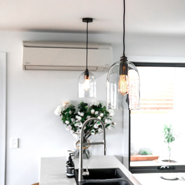 glass dome pendant light with pearl black fitting and a filament globe hanging in a modern kitchen
