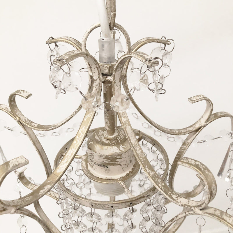 closeup of distressed shabby chic cream chandelier with crystals